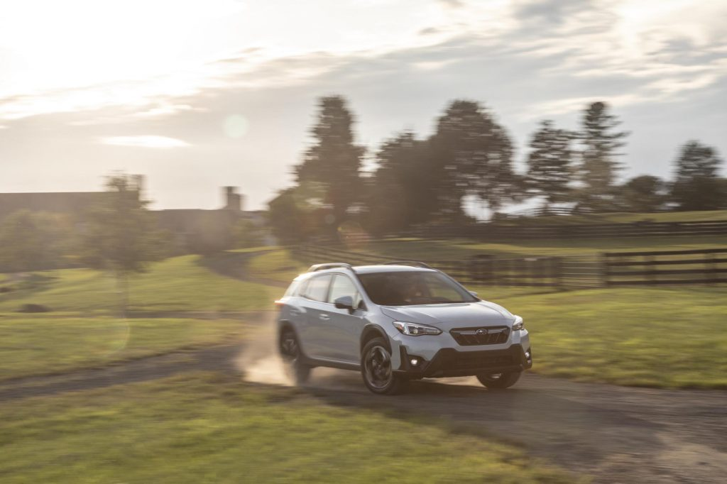 A pearl-white 2021 Subaru Crosstrek subcompact SUV traveling on a dusty country road along rolling hills and brown wooden fences