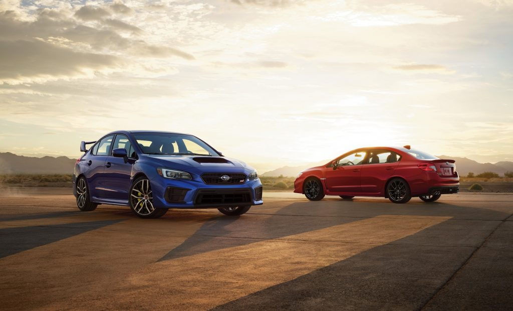 A blue 2021 Subaru WRX STI and a red WRX parked on asphalt in front of mountains