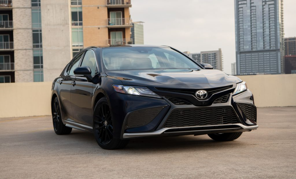 A dark-colored 2021 Toyota Camry XSE Blueprint midsize sedan parked on the roof of a building in a city