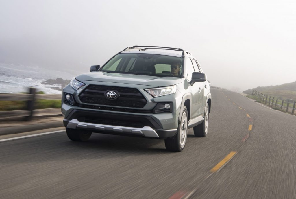 A gray and white 2021 Toyota RAV4 Adventure compact SUV traveling on a two-lane road overlooking a large body of water on a foggy day