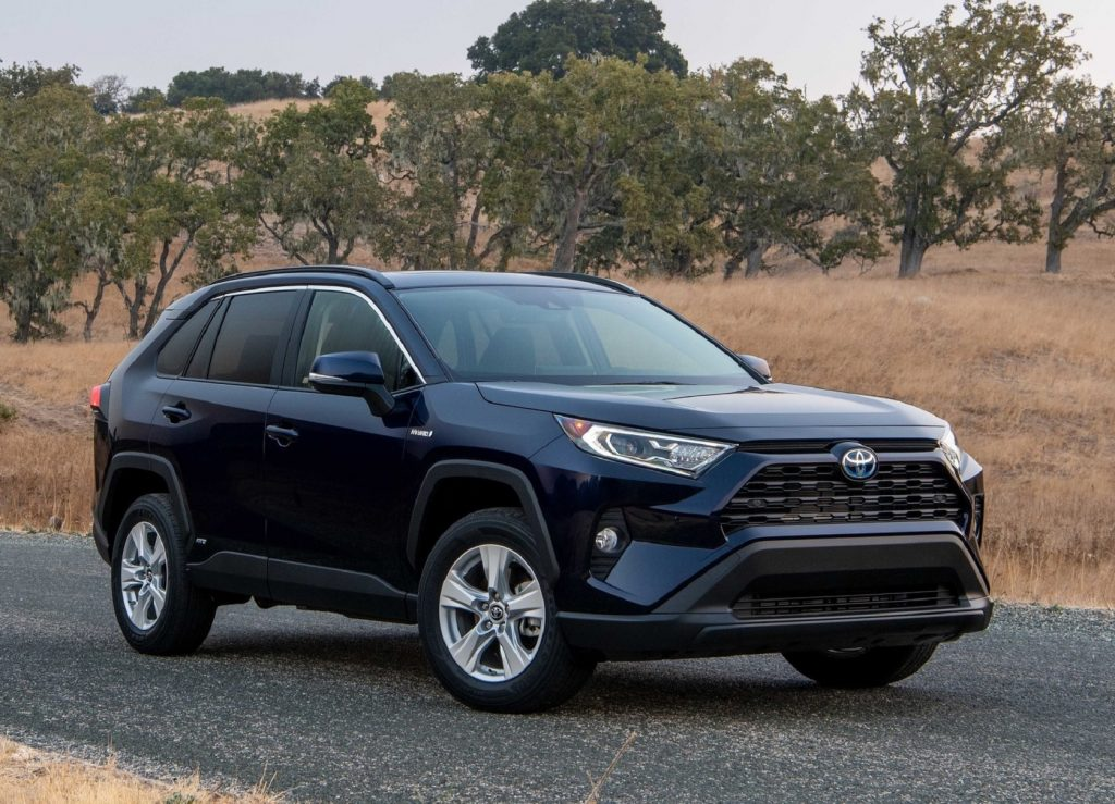 A dark-blue 2021 Toyota RAV4 XLE Hybrid on a plains road