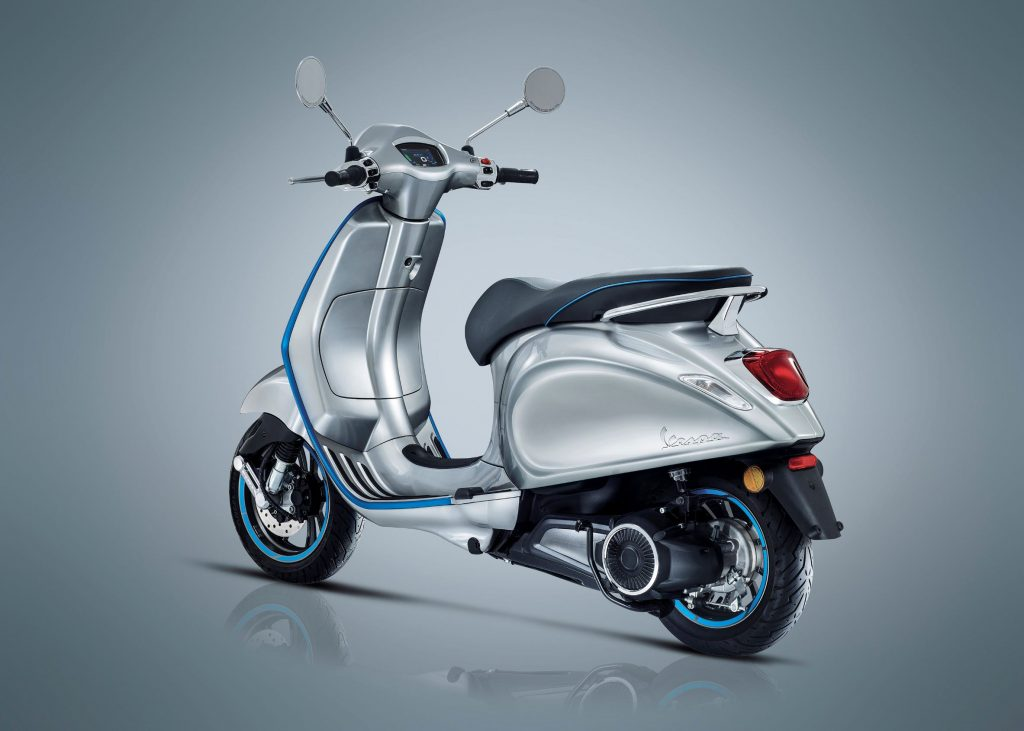 The rear 3/4 view of a silver-and-blue 2021 Vespa Elettrica