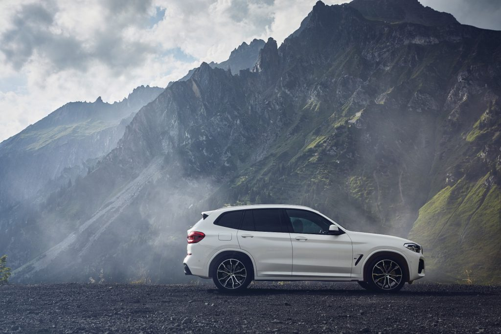 The side profile of a white bmw x3 with mountains in the distance