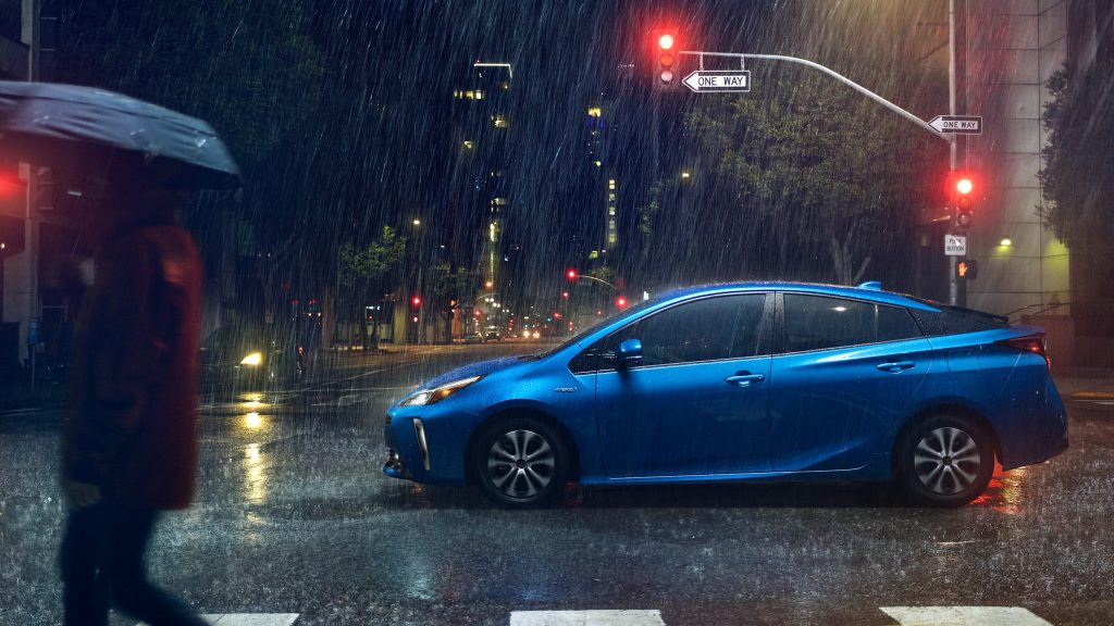 2021 Toyota Prius in blue parked in the rain in a city