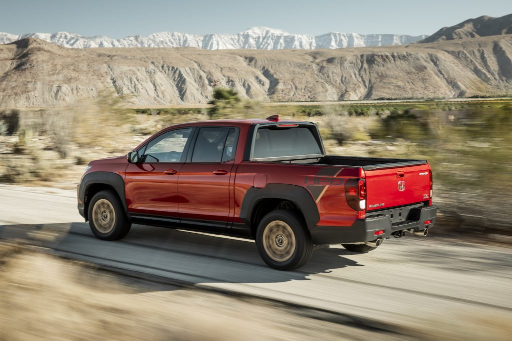 A red 2021 Ridgeline Sport with HPD Package driving on a dirt road