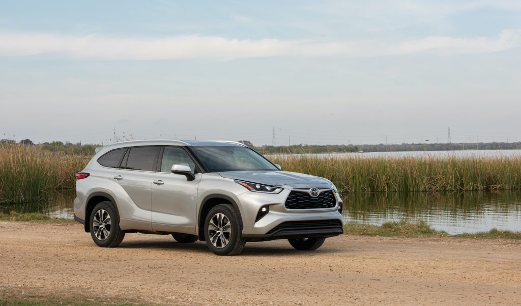 A silver 2021 Toyota Highlander SUV parked near a picturesque pond
