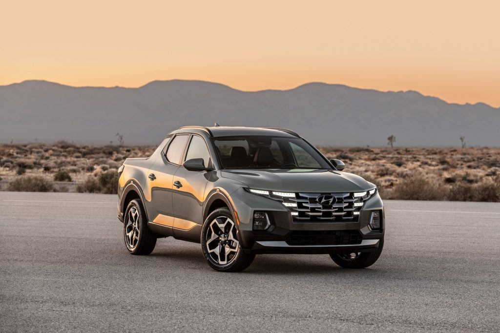 A gray 2022 Hyundai Santa Cruz parked on the pavement in a desert with mountains