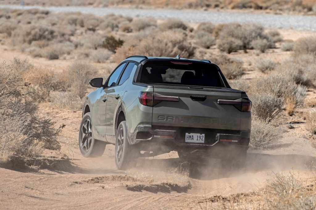 The rear view of a gray 2022 Hyundai Santa Cruz driving through the desert