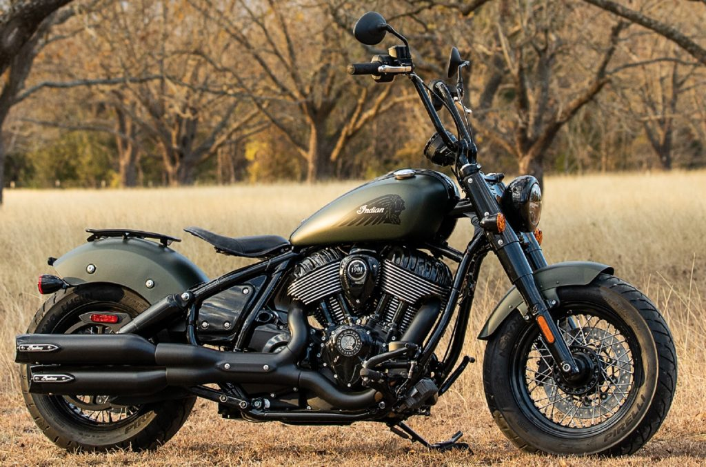 A matte-green 2022 Indian Chief Bobber Dark Horse with Authentic Collection accessories in a forested field