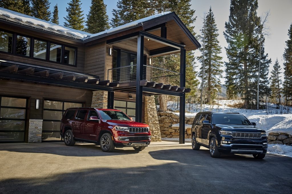 A red 2022 Jeep Wagoneer and a dark-colored 2022 Jeep Grand Wagoneer parked in front of a modern mountain home surrounded by snow and pine trees
