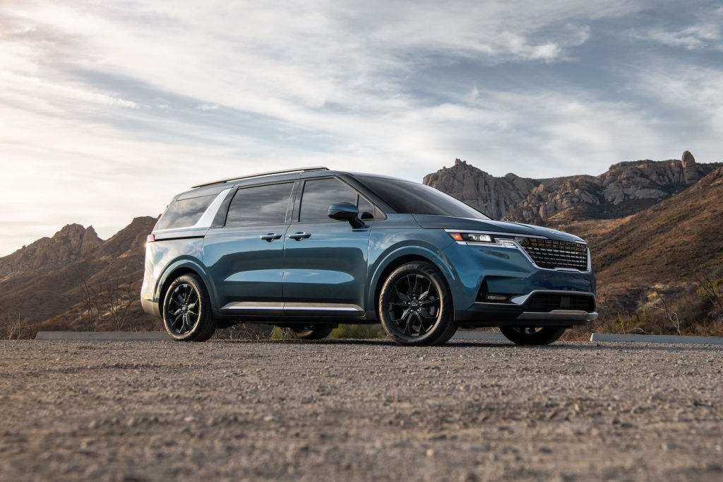 A blue 2022 Kia Carnival minivan parked on gravel in front of mountains on a partly cloudy day