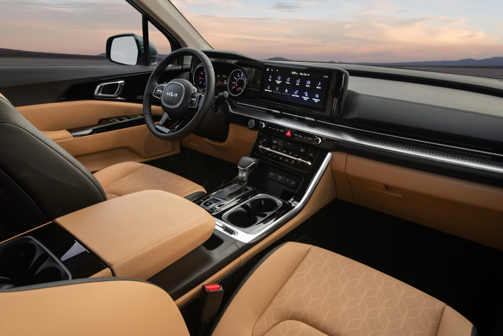 The brown-leather front seats and black dashboard of a 2022 Kia Carnival SX Prestige