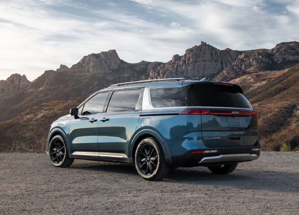 The rear 3/4 view of a blue 2022 Kia Carnival parked by some desert mountains