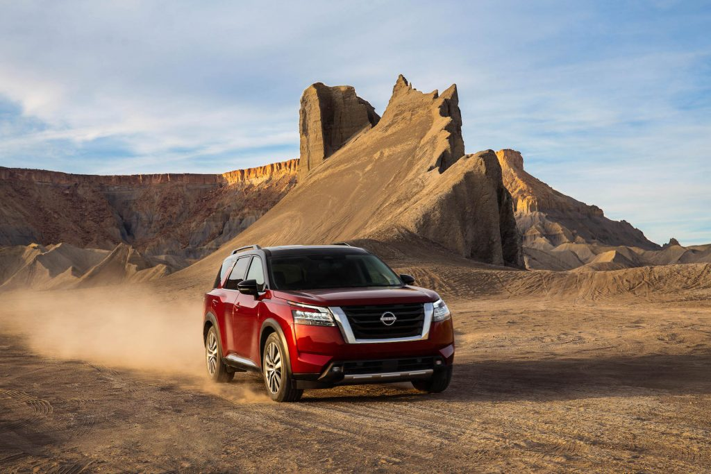 An image of a 2022 Nissan Pathfinder parked outdoors, in the sand..