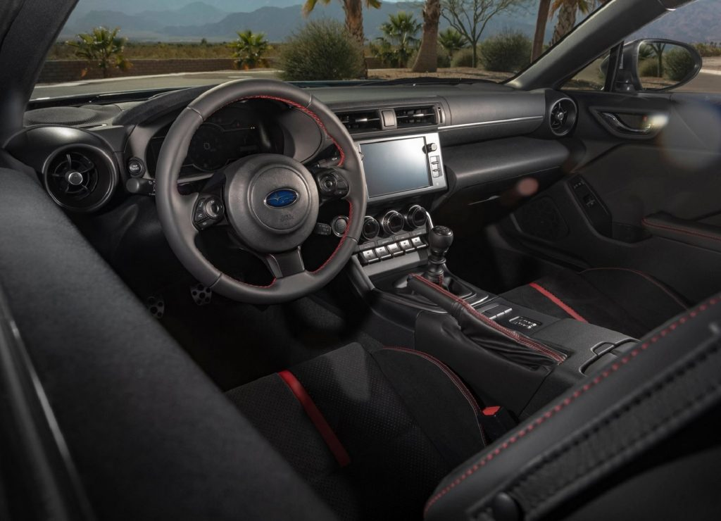 The red-and-black front seats and dashboard of a 2022 Subaru BRZ seen from the drivers-side window