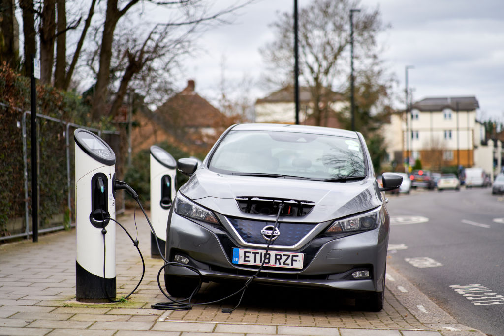 A gray nissan leaf on the charger