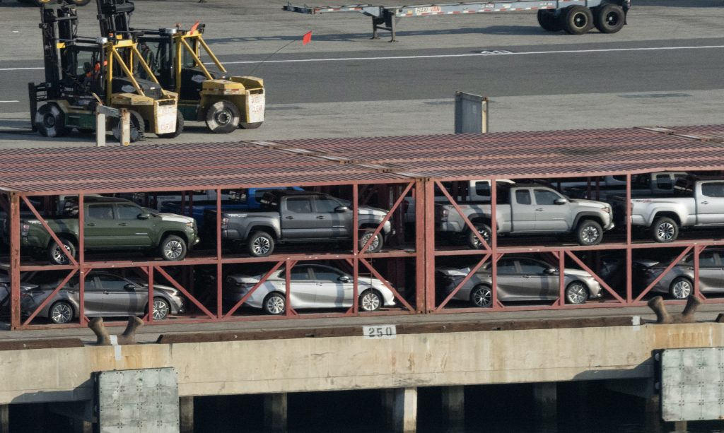 New Toyota Tacoma trucks on a shipping rig with several Camrys in the Port of Los Angeles