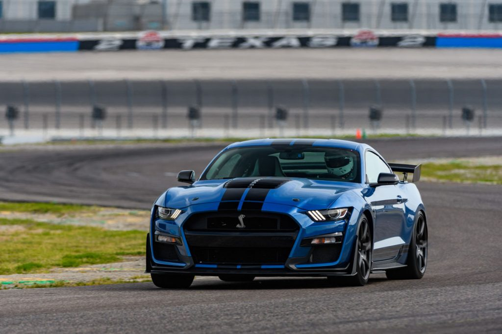 A Shelby GT500 in bright blue paint driving on a track