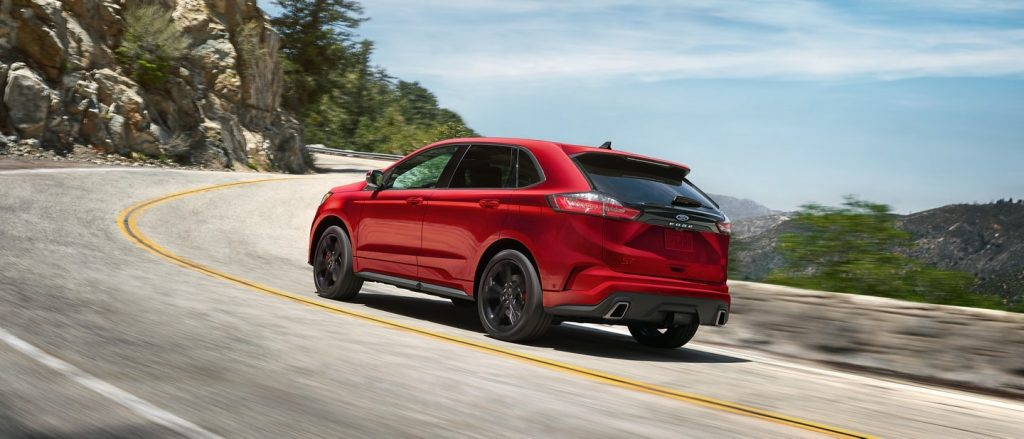a new red ford edge driving on a scene road near lake Huron