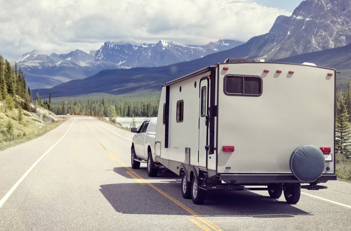 a truck towing a trailer RV camper toward the mountains