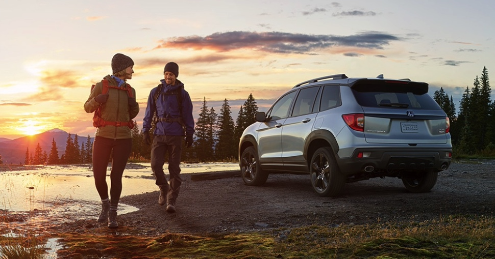 a couple in hiking gear walking away from a 2021 Honda Passport