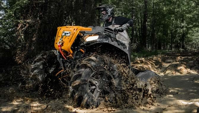 An ATV powering through deep mud with new tires