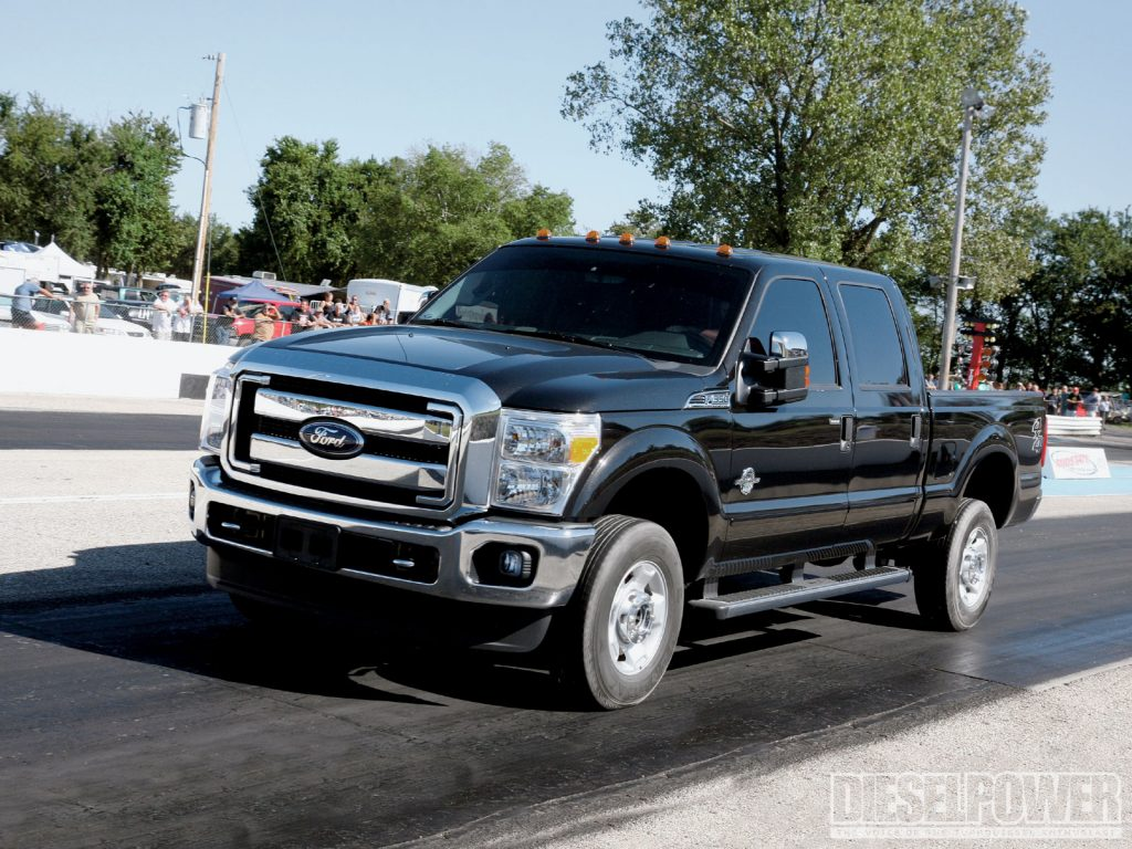 a black 2011 ford f-350 driving on the road