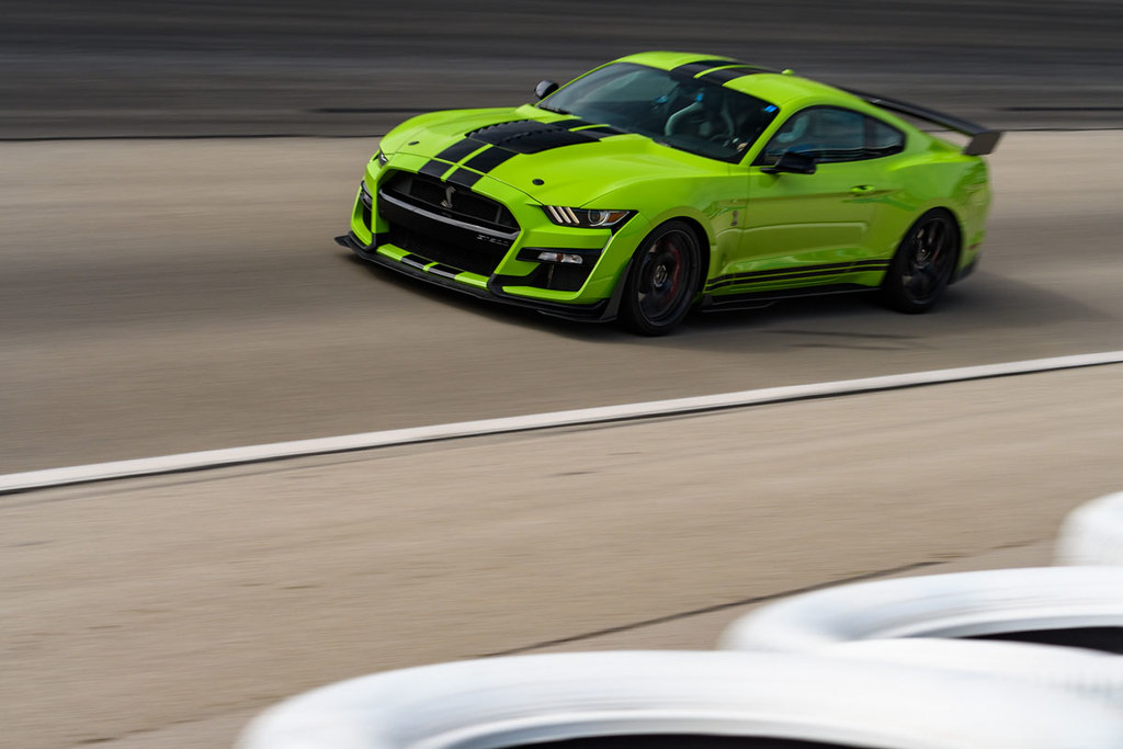a bright green 2021 Shelby gt500 mustang taking a lap on the Texas motor speedway track
