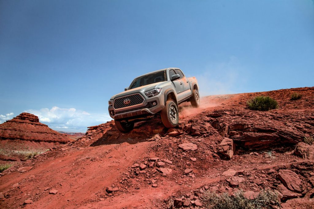 a 2018 Toyota Tacoma crawling down a sandy red hill