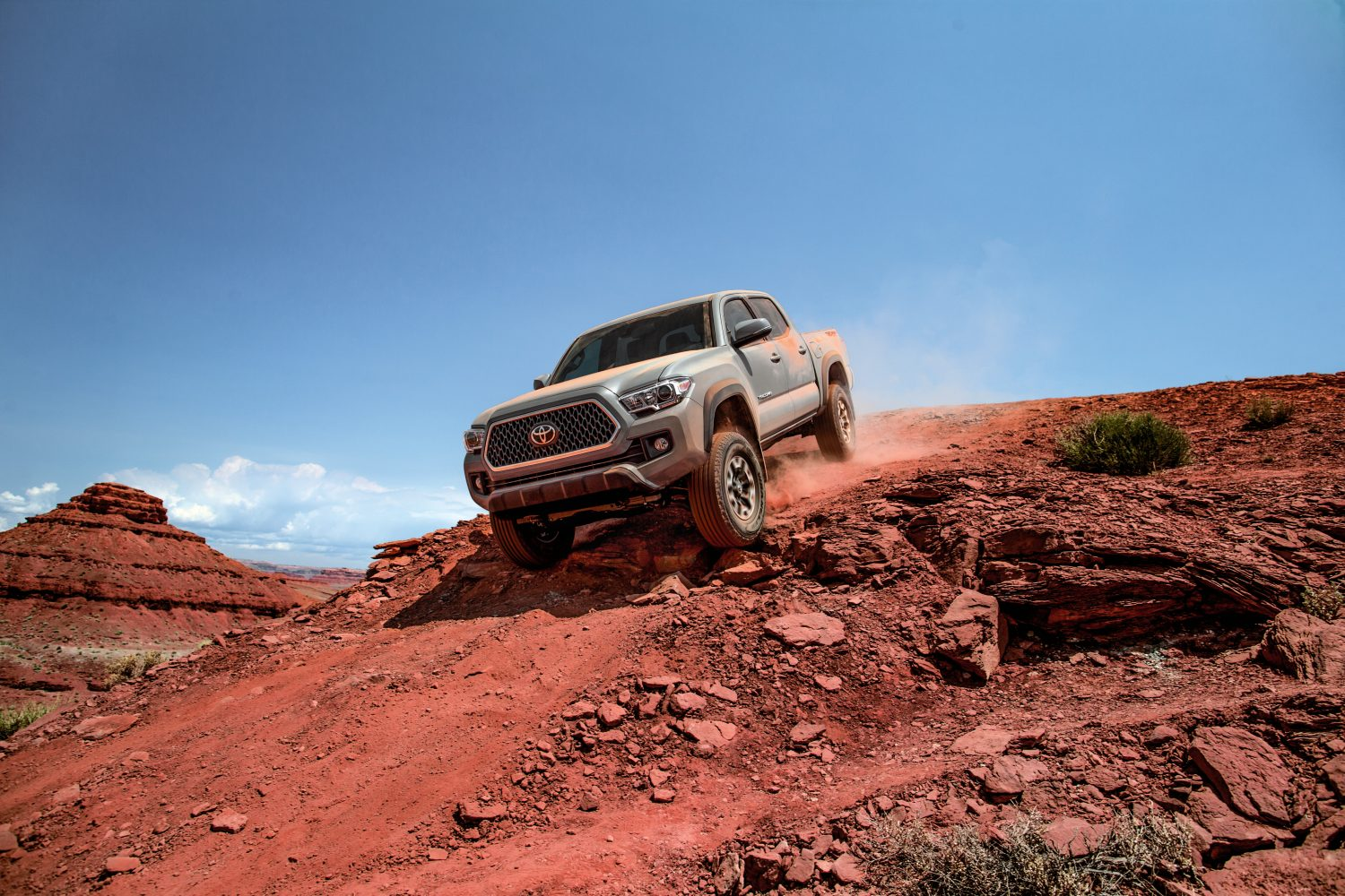 a gray 2018 model year Toyota Tacoma climbing down a sandy red incline on an off-road trail in the desert.