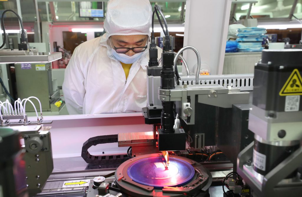 A Jiejie Semiconductor employee makes a silicon wafer destined for microchips in Nantong, China