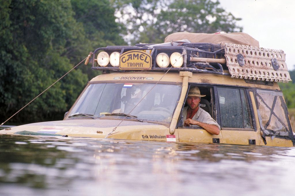 A yellow Land Rover Discovery submerged in a river during the Camel Trophy
