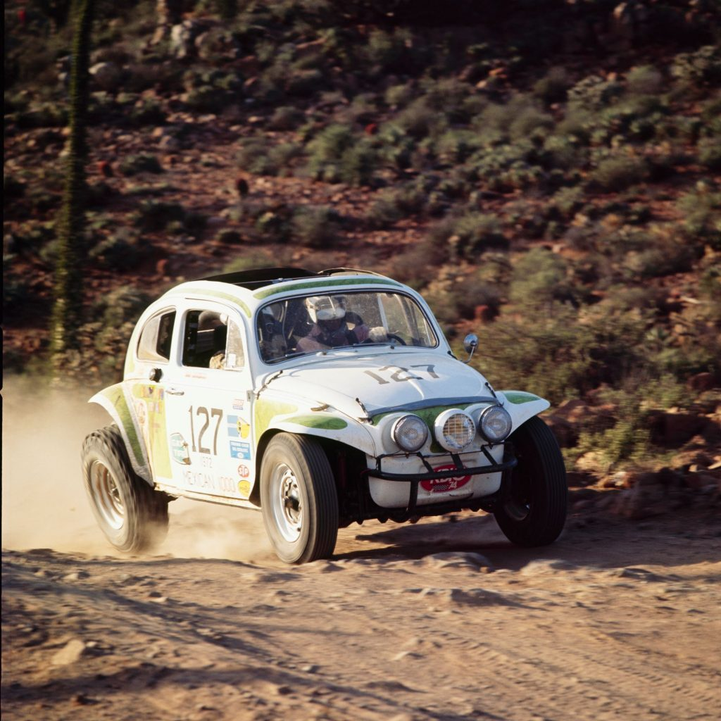 A white-and-green classic Volkswagen Beetle racing in the Baja Peninsula desert in the 1972 NORRA Mexican 1000