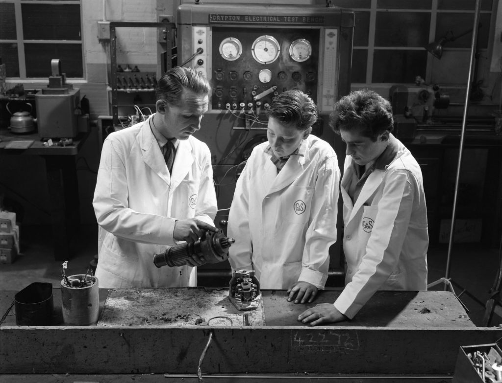 A mechanic trains two apprentices on a starter motor in a garage in 1961