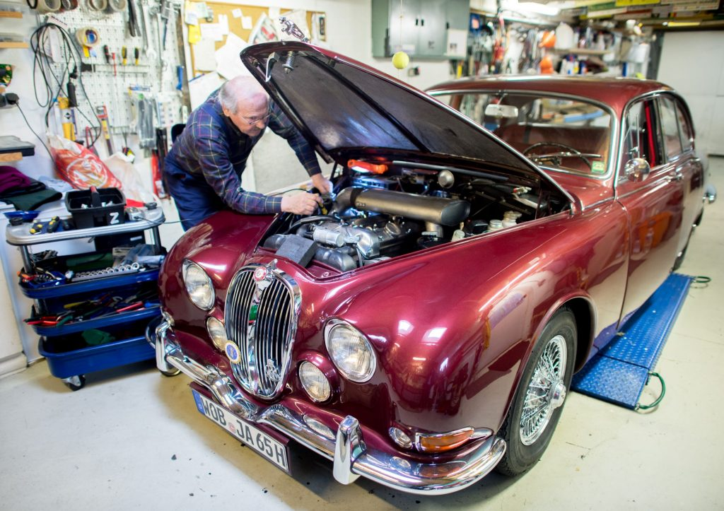 Vintage car collector Horst F. Beilharz examines the inline-six engine of his red Jaguar S-Type in his garage