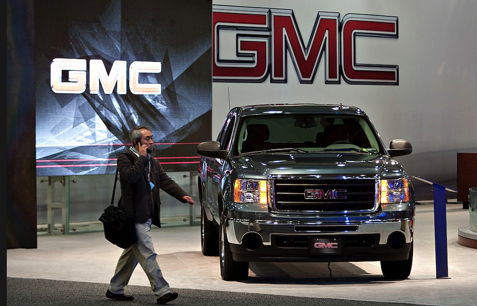 An attendee walks past a 2010 GMC Sierra 1500, a GM pickup truck. during a media preview of the New York International Auto Show.