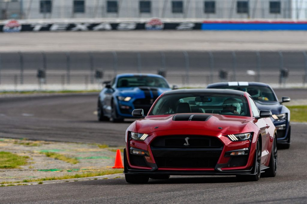 three Gt500 models in a row driving on the track