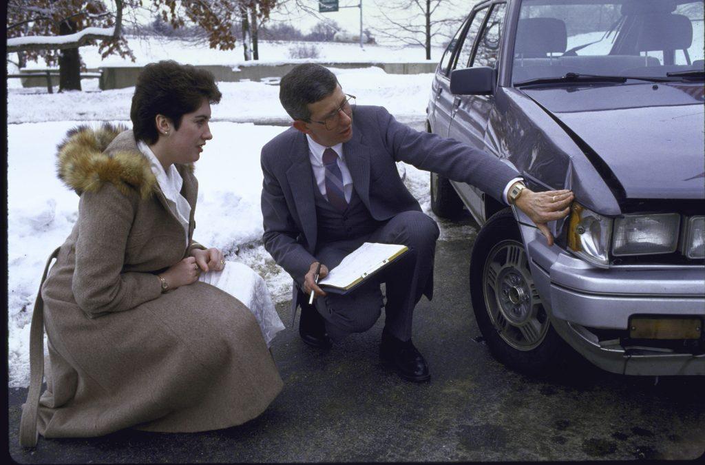Insurance adjuster looking at car damage