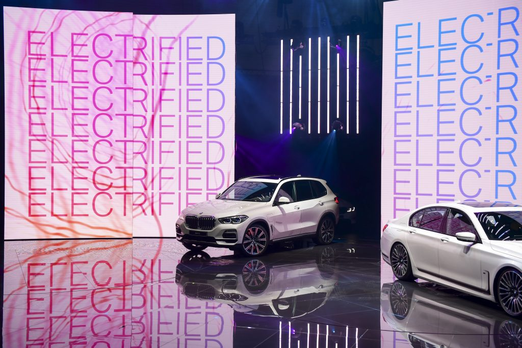 The Bayerische Motoren Werke AG white (BMW) X5 xDrive45e plug-in hybrid sports utility vehicle (SUV) is driven on to a stage on the opening day of the 89th Geneva International Motor Show