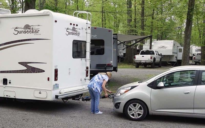 an RV owner hitching a car to tow behind an RV at an RV park