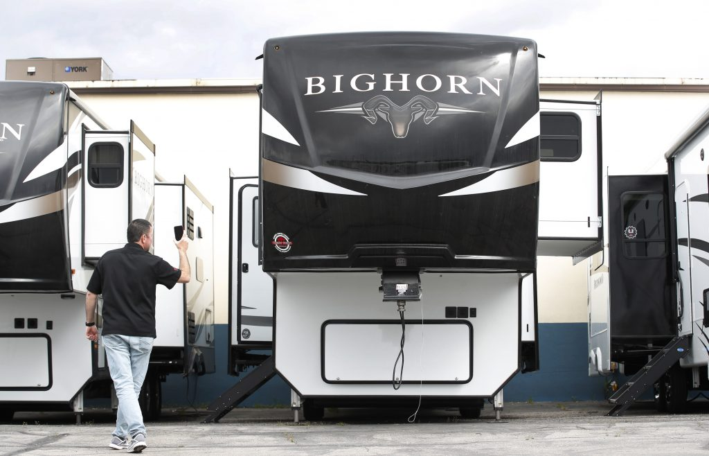 A salesperson holds a mobile device while using video chat to show a potential customer a Heartland Recreational Vehicles LLC Big Horn travel trailer at Motor Sportsland RV dealership