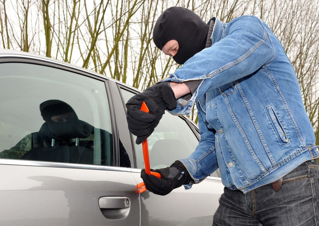 Man wearing a balaclava, holding a wrecking bar, about to break open the side door of a vehicle.