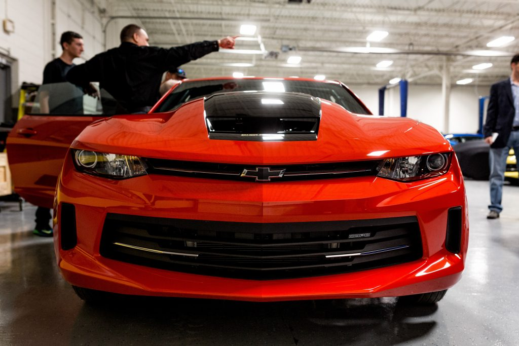 Tour attendees view a General Motors Co. Chevrolet COPO Camaro inside the company's build center in Oxford, Michigan, U.S.