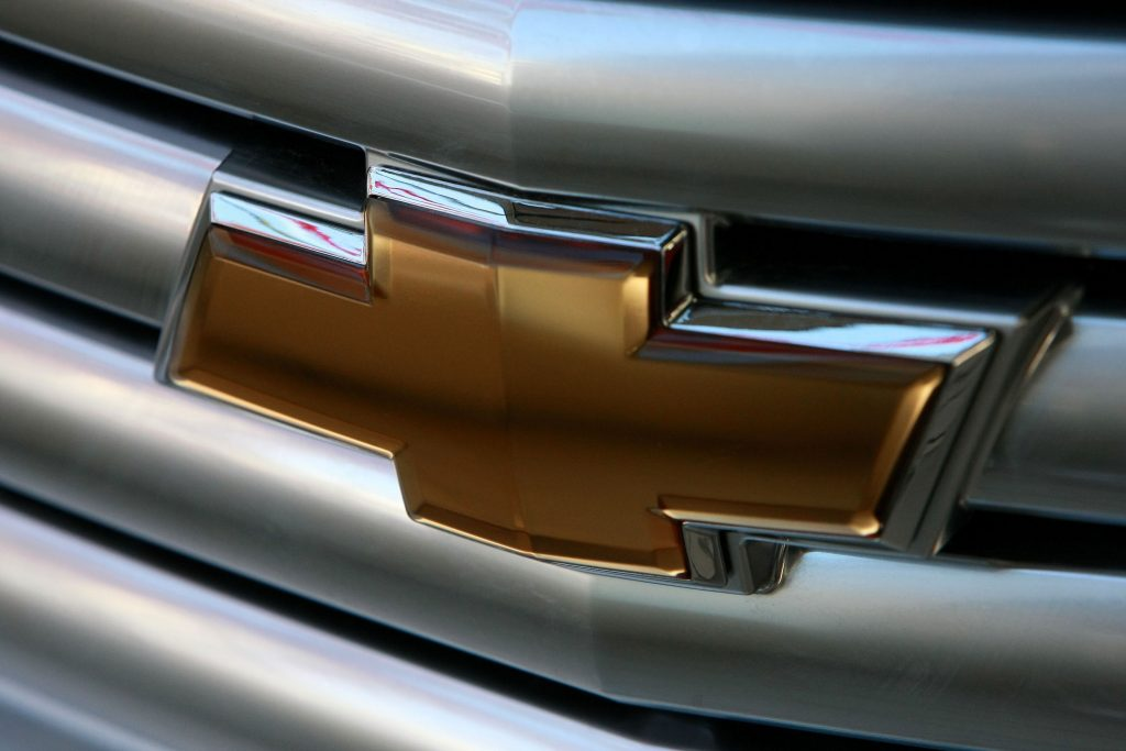 A gold chevy logo on a silver vehicle grille