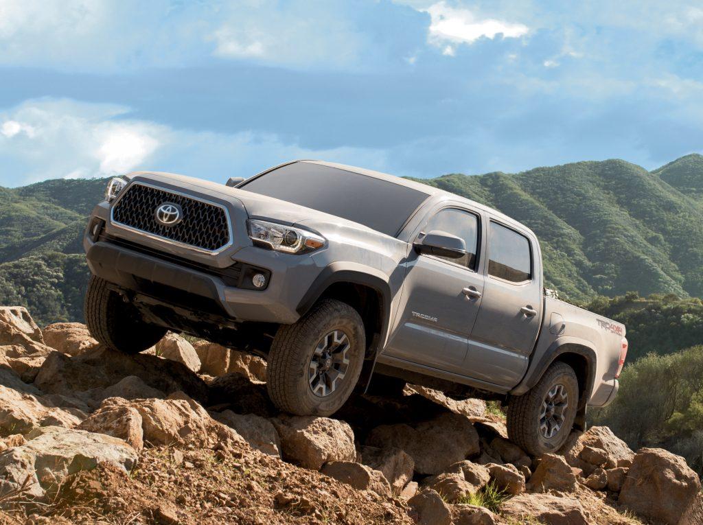 2021 Toyota Tacoma climbing rocks in remote and mountainous terrain.