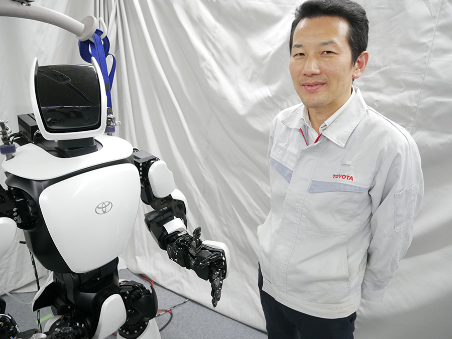 Moridaira standing with the T-HR3 in a development lab