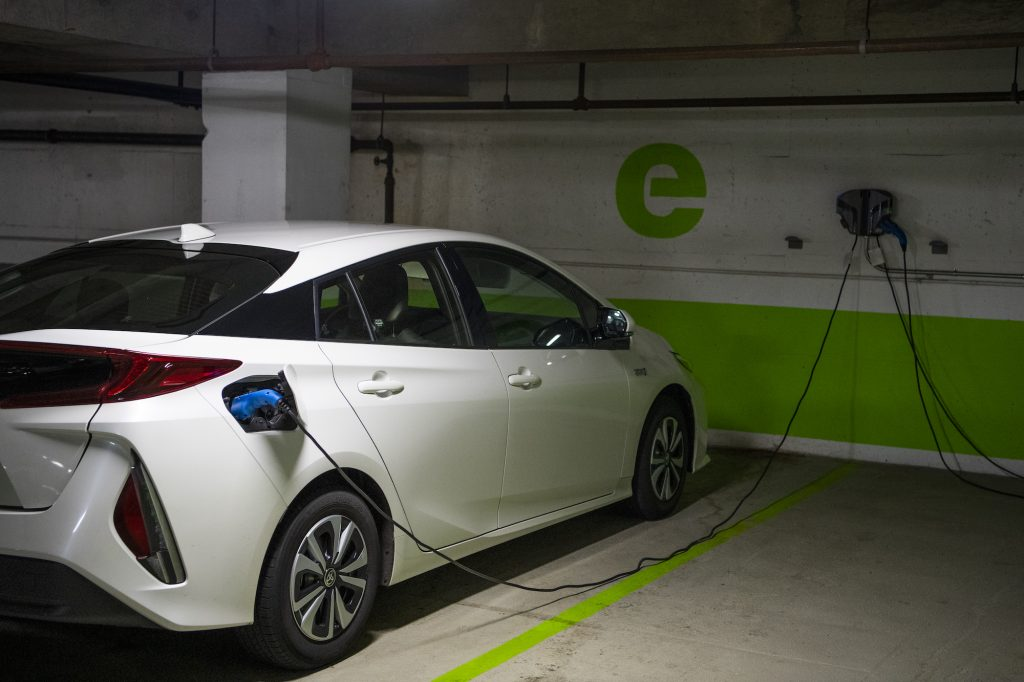 A white Toyota Prius connected to an EV charging station in a Washington, D.C. parking garage on Wednesday, March 31, 2021
