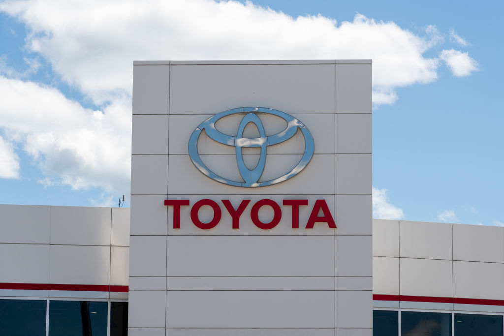 a toyota logo on the side of a dealership with a blue sky in the background