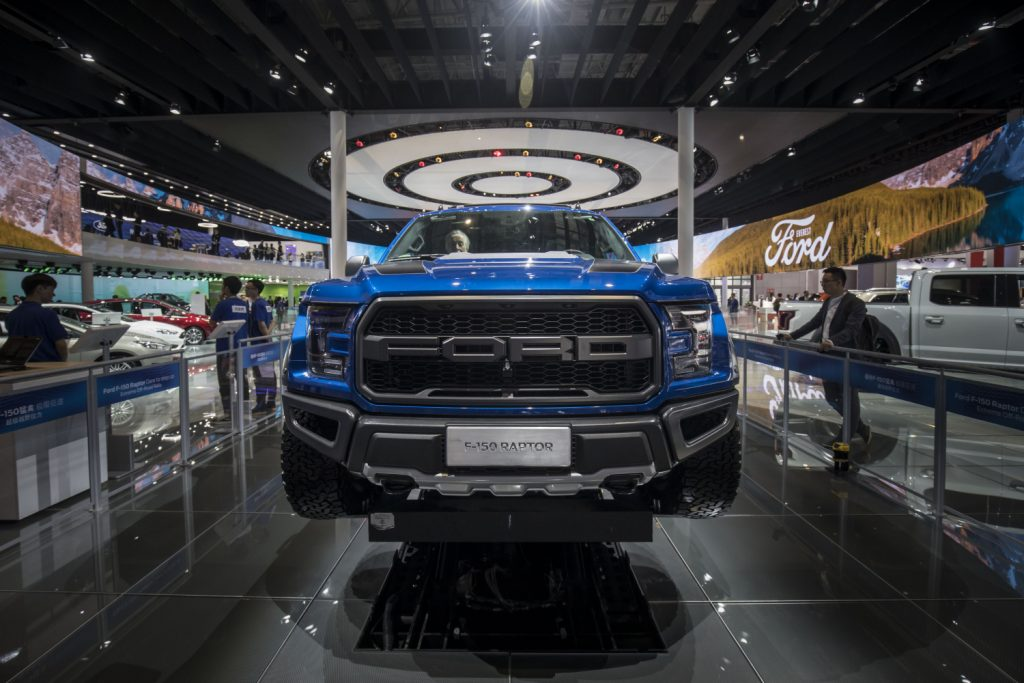 A blue Ford F-150 Raptor on display at an auto show