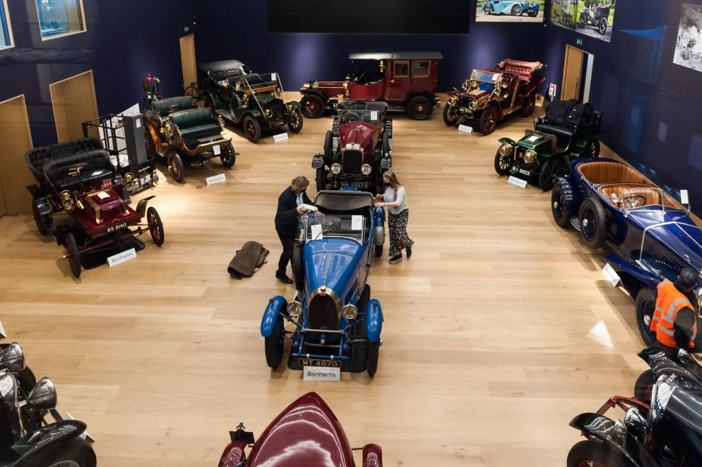 Two employees get some antique and vintage cars ready for an online Bonhams October 2020 auction